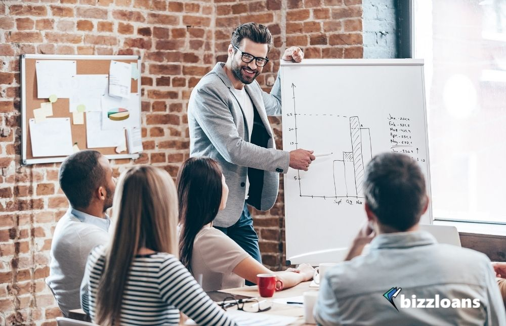 Business owner in glasses standing near whiteboard and discussing about their business growth strategy while his coworkers are listening and sitting at the table