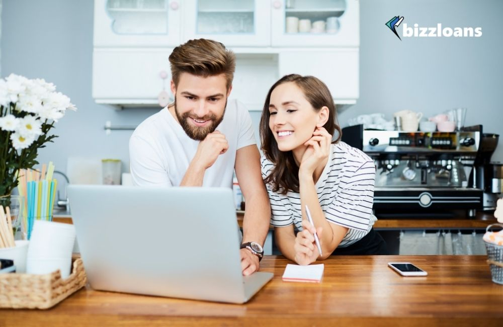 happy couple using a financial tool for their business on a laptop